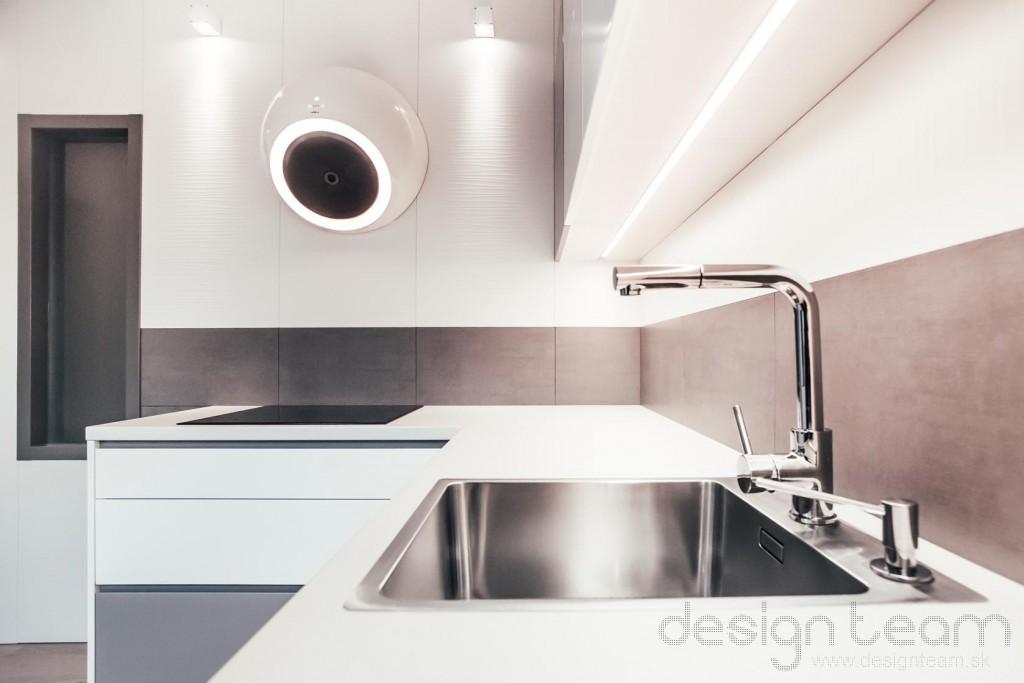 Steny kuchyne sú obložené štruktúrovaným drevotrieskovým obkladom. Nad pracovnú dosku sme dali odolný keramický obklad šedej farby,