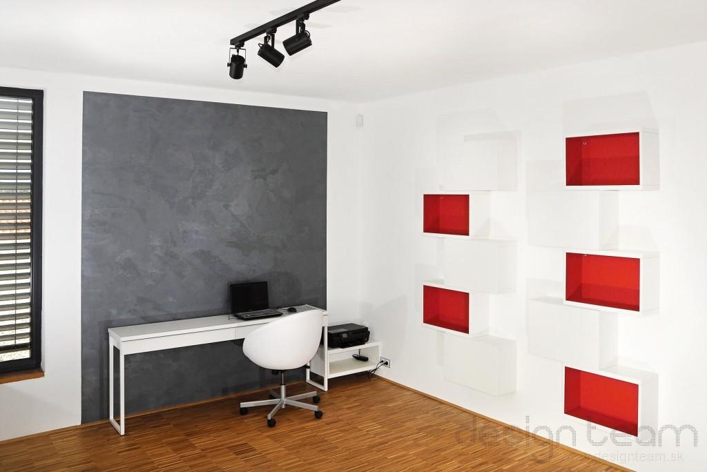 Minimalistický interiér oživuje červená farba tapety v skrinkách a masívna podlaha.