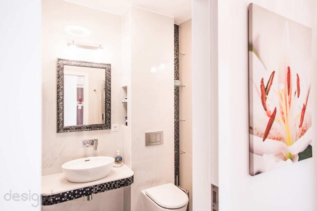 """Pri vstupe do kúpeľne Vás upúta umývadlový kút. Oválne umývadlo je položené na """"murovanom"""" pulte so zaoblenými hranami. Zrkadlo svojim rámom nadväzuje na mozaiku."""